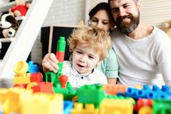 Young family spends time in playroom. Family and childhood. Concept. Mom, dad and boy on light background build out of plastic blocks. Parents watch their son royalty free stock photo