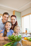 Young family standing behind the kitchen counter Stock Image