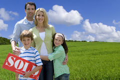 Young family standing in field with sold sign Stock Photos