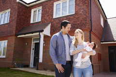 Young Family Standing Outside New Home Stock Photography