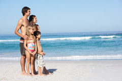 Young Family Standing On Sandy Beach on Holiday Royalty Free Stock Photos