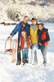 Young Family Standing In Snowy Landscape Stock Photo