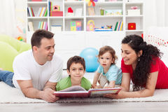 Young family story time with the kids. Laying on the floor together Royalty Free Stock Photo
