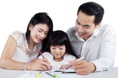 Young family studying together on table Royalty Free Stock Photos