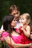 Young family in summer garden. Royalty Free Stock Images
