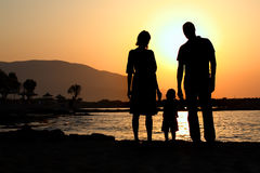 Young family at sunset. Silhouettes of a three person family standing on a beach watching sunset Royalty Free Stock Photo