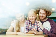 Curious video. Young family with tablet having fun at leisure in shopping center or cafe stock photo