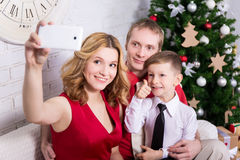 Young family taking selfie photo in front of Christmas tree Stock Photo