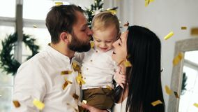 Young family with their cute little toddler being excited with sparkling confetti falling all around celebrating. Christmas at home stock footage