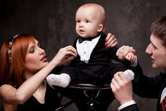 Young family with their son sitting on a chair Stock Photo