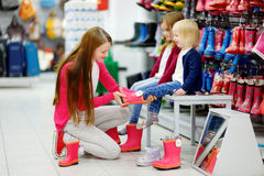 Young family of three choosing new rain boots Stock Photography