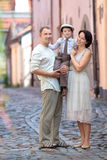 Young family of three in city street Stock Image