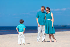 Young family of three having fun tropical beach Royalty Free Stock Images