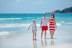 Young family of three having fun tropical beach Stock Images