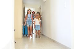 Family with three kids with luggage in hotel room stock photography