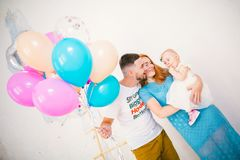 A young family of three people, mom`s dad and daughter`s one year old stands inside the room. Holding a balloon in her hand, a w stock photos