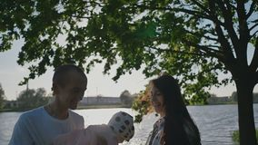 A young family of three people under a green tree on the shore of a lake in the rays of sunlight. Dad holds a small. Daughter in her arms. Summer. Happy stock video footage
