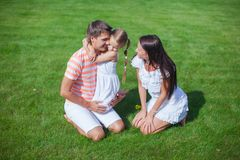 Young family of three sit on the grass and have Stock Images