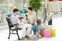 Family shopping. Young family of three sitting on bench in trade center, having talk and relaxing after shopping stock photos