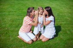 Young family of three sitting on the grass and Stock Images