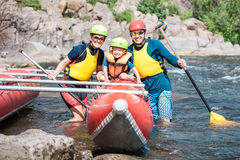 Young family of three wearing life vests and helmets Stock Photography