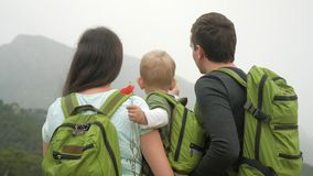 A young family of travelers with a baby looking back at the mountains. Everyone has the same green backpacks. stock video footage