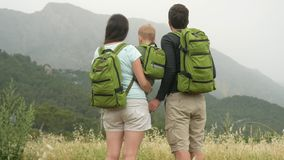 A young family of travelers with a baby looking back at the mountains. Everyone has the same green backpacks. stock footage