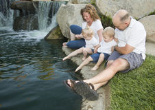 Young Family with Twins Enjoy Water in Park Stock Photos