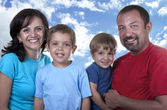Young family with two children. On blue sky Royalty Free Stock Photos