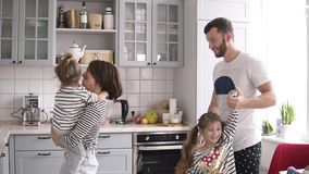 Young family with two daughters are dancing on the kitchen