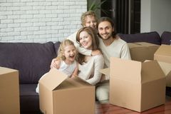 Family with boxes sitting on sofa moving in new home. Young family with two kids sitting on sofa embracing, parents with son and daughter hugging on couch Stock Photos