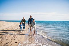 Young family with two small children running outdoors on beach. Young family with two small children running barefoot outdoors on beach royalty free stock image