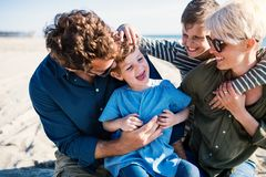 Young family with two small children sitting outdoors on beach, having fun. Portrait of young family with two small children sitting outdoors on beach, having stock image