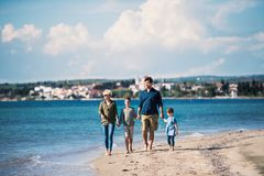 Young family with two small children walking outdoors on beach. Young family with two small children walking barefoot outdoors on beach royalty free stock image