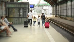 Young family of two spouses, son and daughter, running to catch the train before it leaves the railway station without. Them, parents and children traveling and stock footage