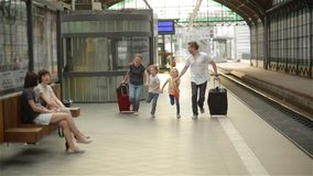 Young family of two spouses, son and daughter, running to catch the train before it leaves the railway station without. Them, parents and children traveling and stock video