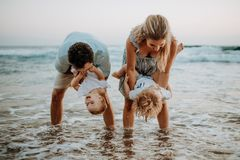 A young family with two toddler children having fun on beach on summer holiday. stock images