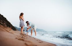 A young family with two toddler children standing on beach on summer holiday. royalty free stock photo