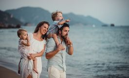 A young family with two toddler children standing on beach on summer holiday. A young family with two toddler children standing on beach on summer holiday royalty free stock photos