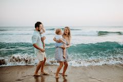 Young family with two toddler children walking on beach on summer holiday. stock images