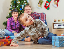 Young family under the christmas tree at home Stock Images