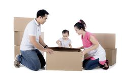 Young family unpacking cardboard on studio Royalty Free Stock Images