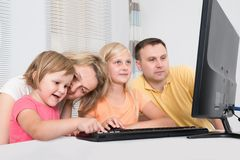 Young family using computer together Royalty Free Stock Images