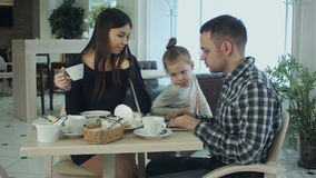 Young family using laptop, chatting and smiling in cafe or restaurant. stock video