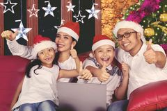 Young family using a laptop at Christmas time Stock Image