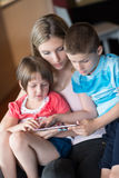 Young Family Using A Tablet To Make Future Plans Royalty Free Stock Image