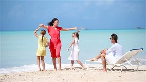 Young family on vacation have a lot of fun. Mother dancing on the beach with her beautiful kids stock footage