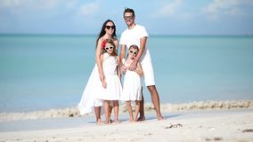 Young family in white on vacation on caribbean beach stock video