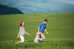 Young family on a walk against green fields and hills Stock Photo
