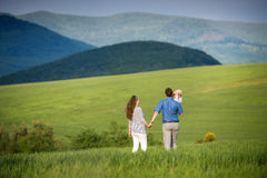Young family on a walk against green fields and hills Royalty Free Stock Photography